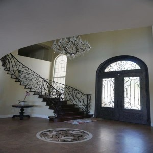 Front entrance interior with arched double doors and radius staircase