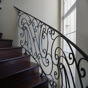 Wooden staircase with wrought iron from wall
