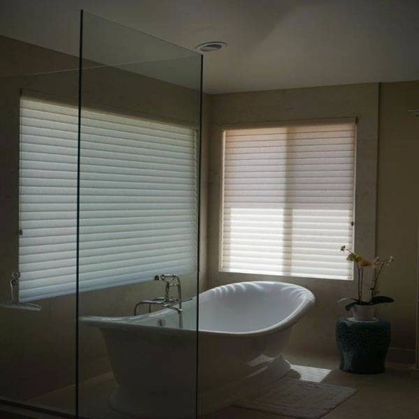 Windows adding light and privacy to a remodeled custom bathroom with a claw foot tub