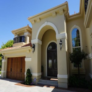 Exterior of a beautiful Mediterranean style home with large doors and windows in North San Diego County Encinitas, CA